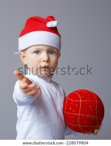 Portrait of Caucasian baby with blue eyes wearing a Santa hat and white shirt standing on a light background holding red golden chinese ball and giving welcome hand, New Year concept, studio - stock photo