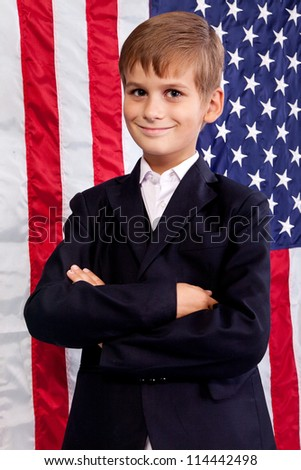 Portrait of Caucasian boy with arms crossed with American flag in background. - stock photo