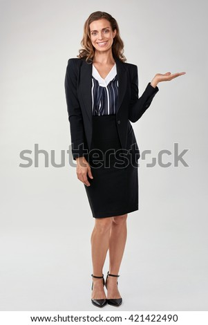 Portrait of caucasian business woman presenting in studio, isolated on grey - stock photo