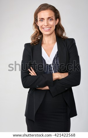Portrait of caucasian business woman standing with arms crossed in studio, isolated on grey - stock photo