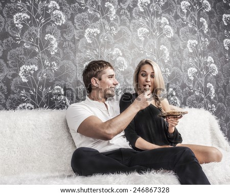 Portrait of caucasian couple sit on white wool couch together eat cookie Man holding and feed woman sweet cookie between lips Girl bite food Empty texture pattern wallpaper Copy space for inscription - stock photo