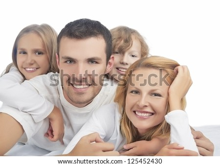 portrait of caucasian family members in group laying on sofa isolated over pure white - stock photo