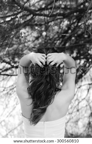 Portrait Of Caucasian Female Model Wearing Strapless White Dress Posing Near Forest Running Her Fingers Through Her Hair With Back Turned & Face Not Showing In Black & White  - stock photo