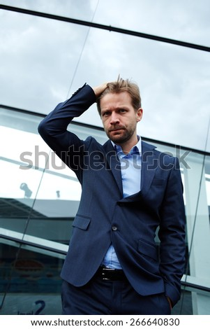 Portrait of caucasian frustrated businessman with hand behind his head, young worried business man with bad headache holding head in pain while standing against office building - stock photo