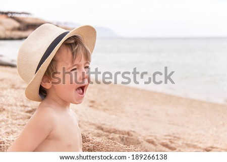 Portrait of caucasian happy baby (boy) in the hat. Child is laughing and shouting in summer day at the beach. Kid is enjoying serene sea.  Copy space, outdoor, close up (Sharm El Sheikh, Egypt). - stock photo