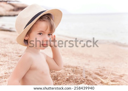 Portrait of caucasian happy baby (boy) in the hat. Child is smiling in summer day at the beach. Kid is enjoying ocean. Image has copyspace for text. Outdoor, close up. (Sharm El Sheikh, Egypt). - stock photo