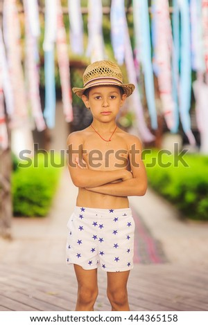 Portrait of caucasian happy baby (boy) in the hat. Child is smiling in summer day at the beach. Kid is enjoying ocean. Boy wearing a sun hat grinning happily at the camera. - stock photo