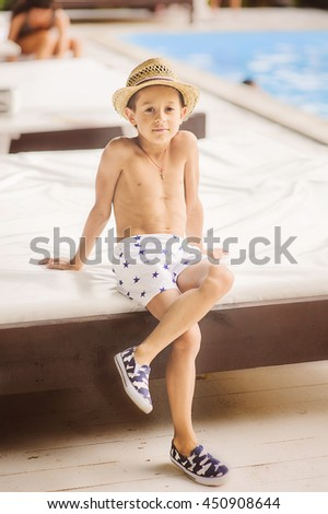 Portrait of caucasian happy baby (boy) in the straw  hat. Child is smiling in summer day. Kid is enjoying summer. Image has copyspace for text. Outdoor, close up. - stock photo