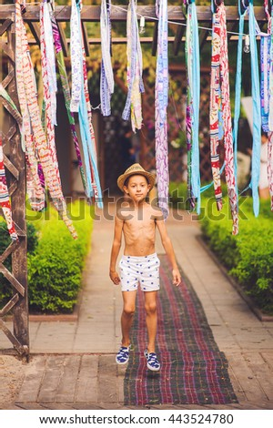 Portrait of caucasian happy baby (boy) jumping in the hat. Child is smiling in summer day at the beach. Kid is enjoying ocean. Boy at the beach wearing a sun hat grinning happily at the camera.  - stock photo