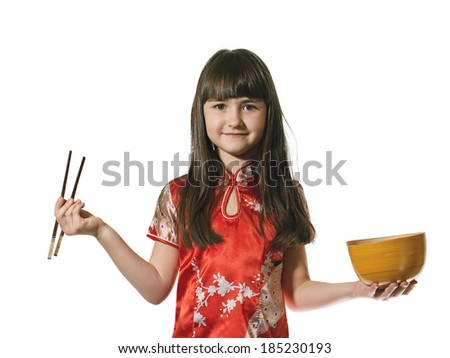 Portrait of caucasian little girl in vietnamese national costume eat a wooden bowl by chopsticks isolated on white