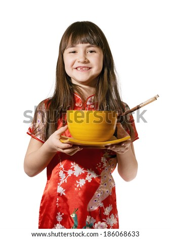 Portrait of caucasian little girl in vietnamese national costume keep wooden bowl and plate isolated on white