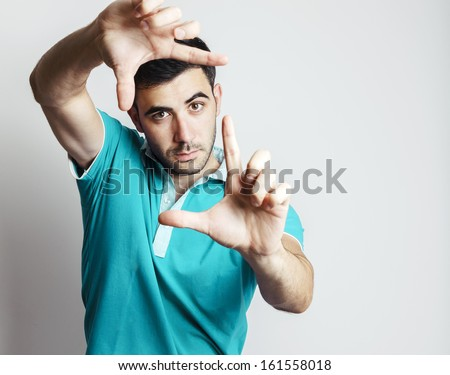 Portrait of caucasian male making photo frame with his hands against grey background - stock photo