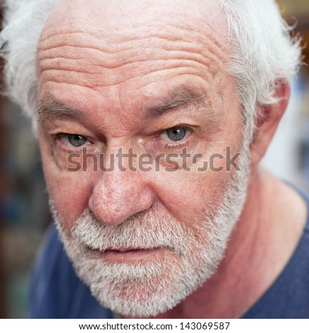 Portrait of caucasian man. Blue eyes, white beard, neutral expression.