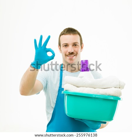 portrait of caucasian man holding basket with laundry, smiling and showing ok sign, on white background - stock photo
