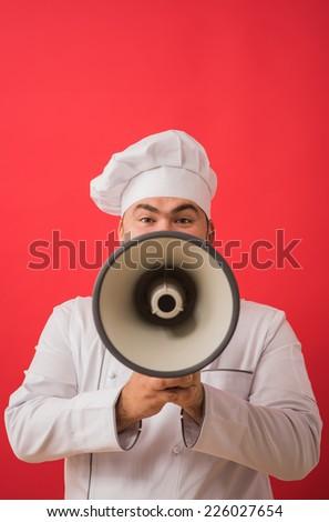 Portrait of caucasian man with chef uniform holding megaphone - stock photo