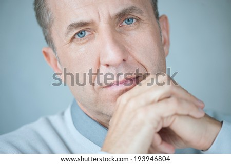 Portrait of caucasian mature business man with hands on chin, looking at camera. Horizontal shape, head and shoulders, front view, copy space - stock photo