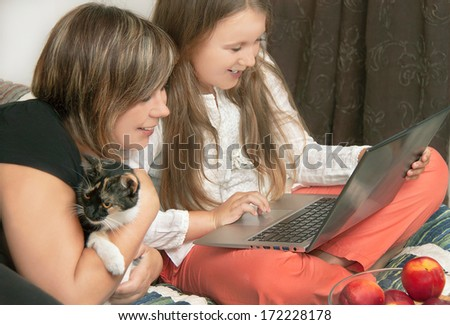 Portrait of caucasian mother and daughter using laptop  with smile. Woman and girl are sitting in the bedroom with cat. Happy, cute positive models. Indoor, clous up. - stock photo