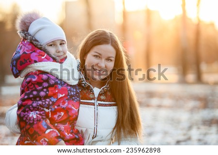 Portrait of Caucasian mother with a child, a frosty evening, sunshine, sunset - stock photo