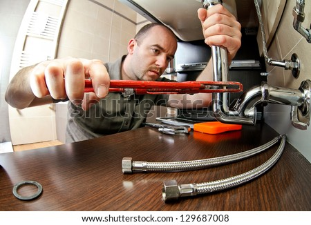portrait of caucasian plumber at work - stock photo