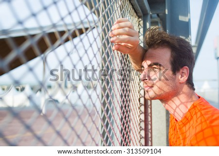 Portrait of caucasian sports man leaning on urban metal fence while rest after active training and enjoying beautiful sunset, young thoughtful caucasian male runner taking break after workout outdoors - stock photo