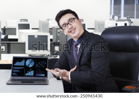 Portrait of caucasian worker showing financial chart on laptop computer while smiling friendly - stock photo