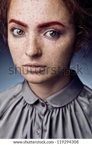 Portrait of  caucasian young woman with freckles posing on grey background - stock photo