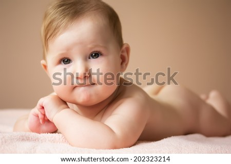 Portrait of charming baby girl lying on her stomach