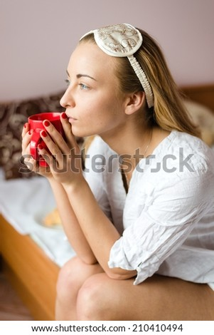 portrait of charming beautiful dreamy young woman with a sleep mask & cup of hot drink sitting on the bed and looking out the window - stock photo