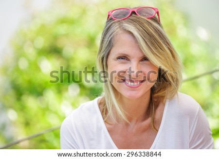 Portrait of charming blond woman of middle-aged smiling in glasses  - stock photo