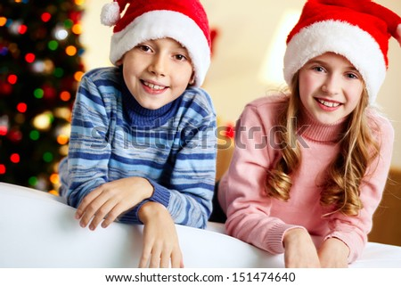 Portrait of charming brother and sister enjoying Christmastime - stock photo