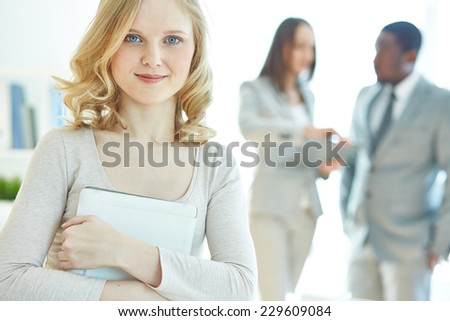 Portrait of charming businesswoman with touchpad looking at camera - stock photo