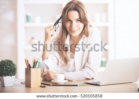 Portrait of charming caucasian female sitting at office desk with laptop, coffee cup, supplies and other items