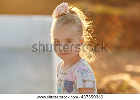 Portrait of charming girl in a dress at sunset with glowing hair backlit summer