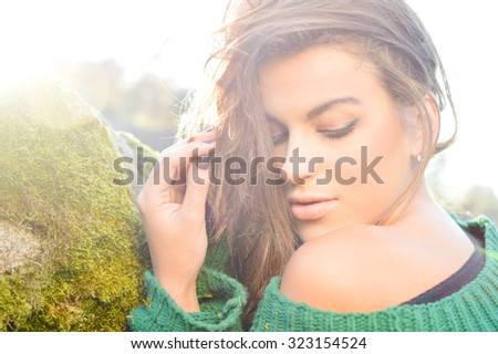 Portrait of charming girl in green sweater looking down. Young woman with naked shoulder on lens flare outdoor background. - stock photo