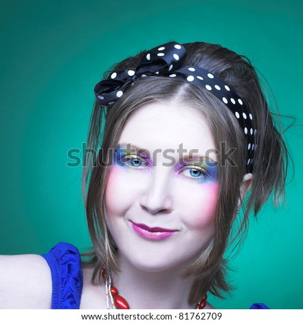 Portrait of charming girl in summer dress with creative make-up and with lollipop.