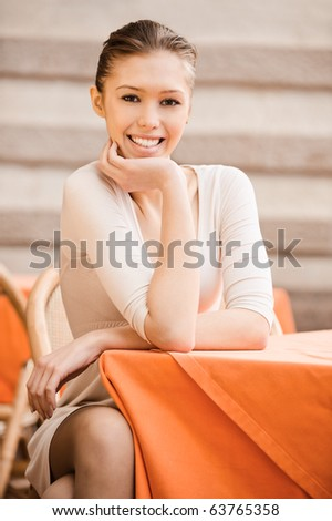 Portrait of charming girl which sits at little table in cosy cafe. - stock photo