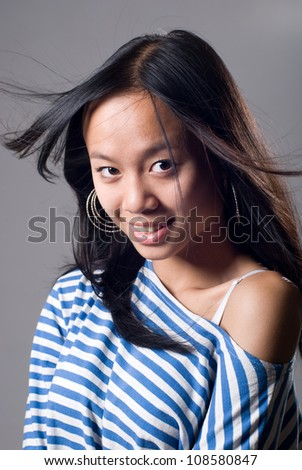 Portrait of charming girl with a flying hair.Asian girl isolated on grey background.