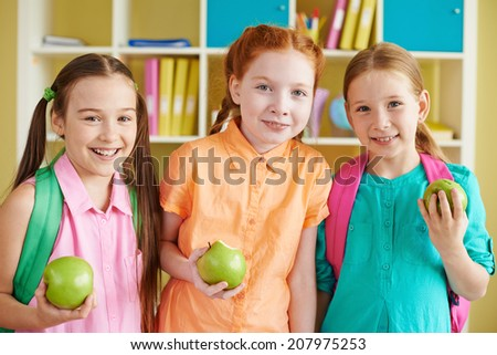 Portrait of charming girls with backpacks and green apples looking at camera