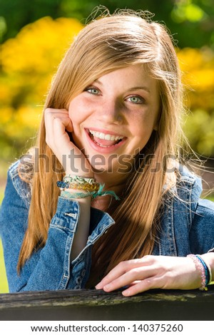 Portrait of charming happy young girl on sunny day - stock photo