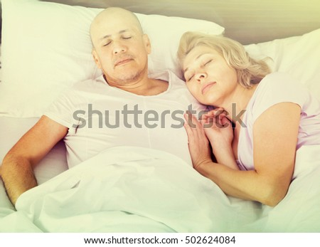 Portrait of charming ordinary mature couple napping in bed with closed eyes