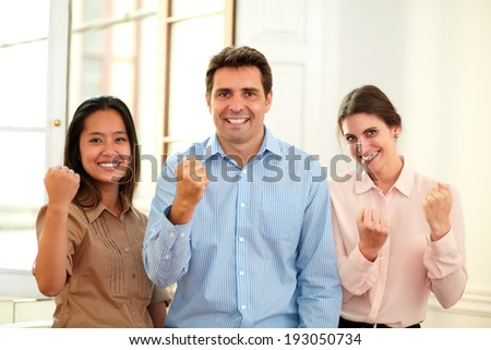 Portrait of charming professional team with winning sign smiling at you while standing on office background