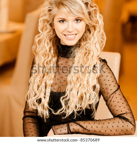 Portrait of charming smiling curly-haired young woman with curly hair, sitting at table against beautiful interior.