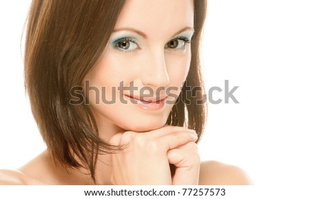 Portrait of charming smiling young woman with bared shoulders which touches fingers cheek, on white background.