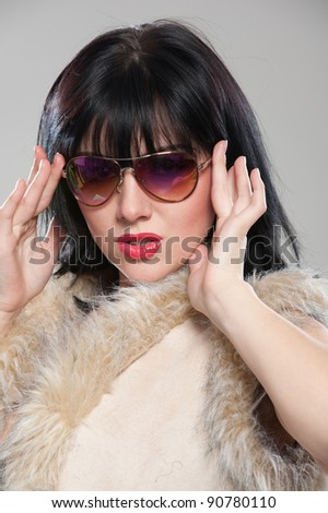 Portrait of charming stylish young woman in sunglasses posing in the studio on gray background - stock photo