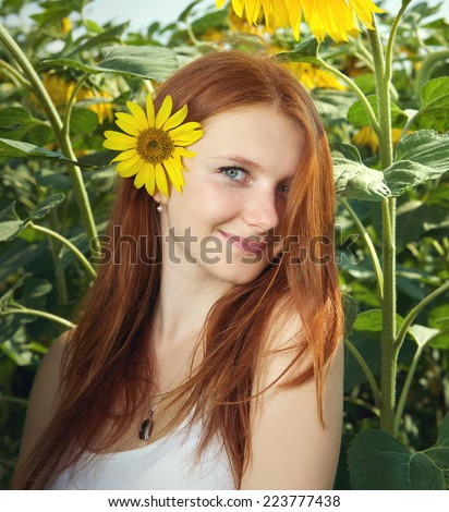 Portrait of charming young girl with beautiful red hair. The sunflower field, summertime  - stock photo
