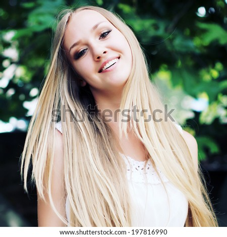 Portrait of charming young girl with long hair. Attractive young woman walking in a park on a sunny day. Photo toned style Instagram filters  - stock photo