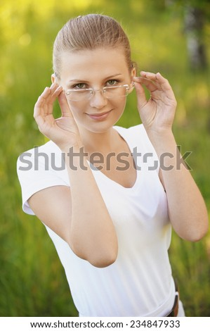 Portrait of charming young smiling woman in glasses on green background of city park.