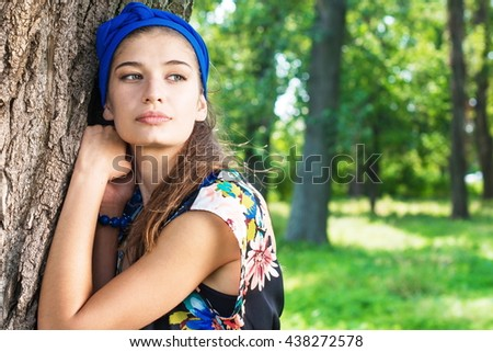 portrait of charming, young woman, holding her hand beside her cheeks background summer green park - stock photo