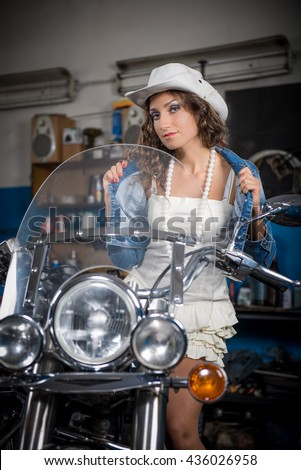 Portrait of charming young woman with curly hair. girl on a motorcycle. beautiful girl sitting on a motorcycle in the garage.