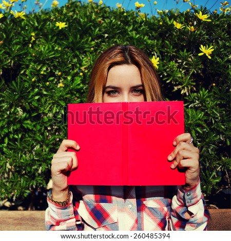Portrait of charming young woman with pink book held up close to her face, cute female covering half face with a book while standing on spring green hedge with flowers background, filtered image